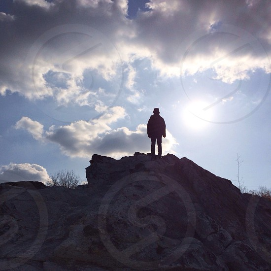 man standing on rock facing sunrise view photo