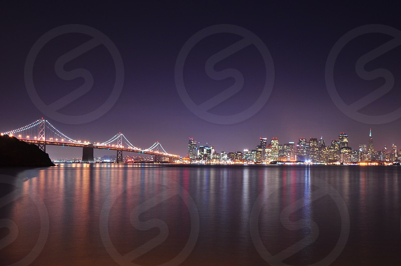 skyline lights reflected on the water at san francisco by night from treasure island photo