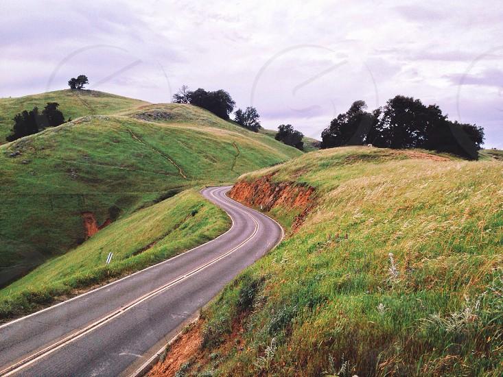 grey concrete road near the green hill photo