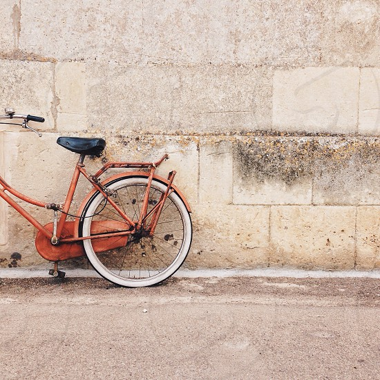 red cruiser bicycle leaning on wall photo