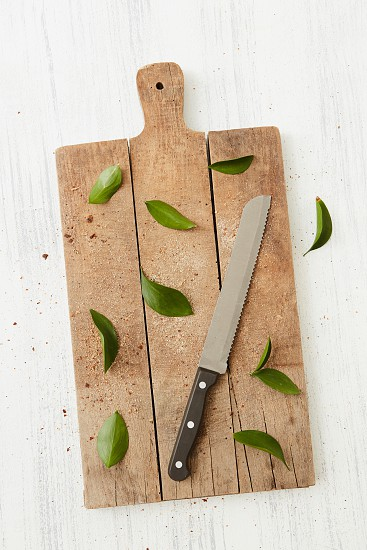 Kitchen wooden board with knife and green leaves on white background flat lay photo