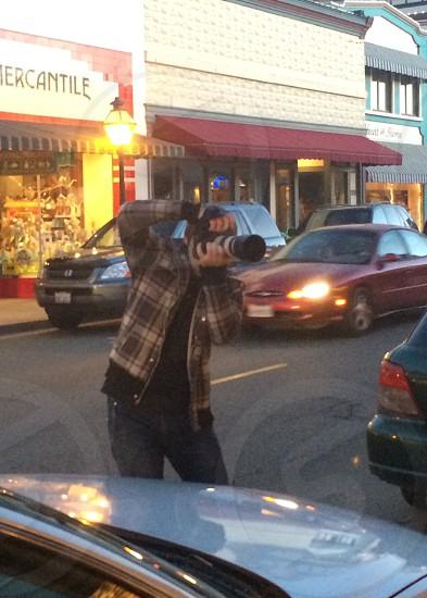 man wearing brown plaid jacket black trim and jeans photo