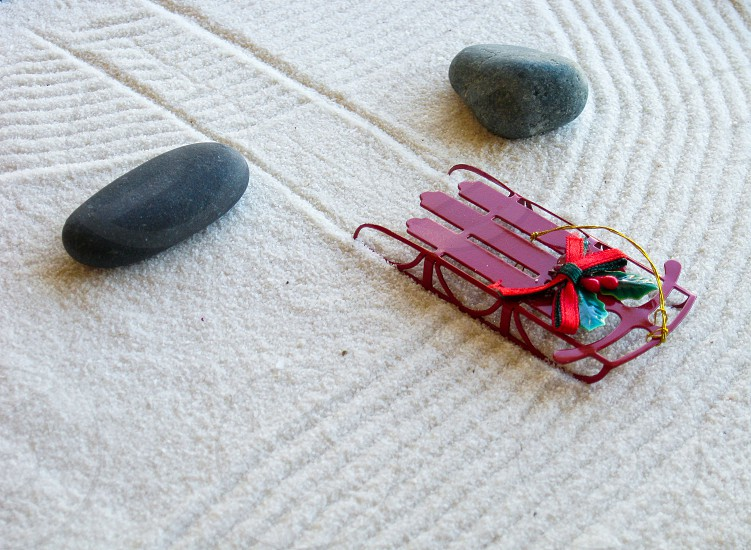 A red snow sled makes tracks between smooth rock in a miniature Zen sand garden as symbol of peaceful and calm Christmas and winter holidays. photo