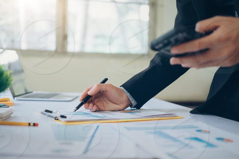 Businessman using smartphone to analyze information. photo