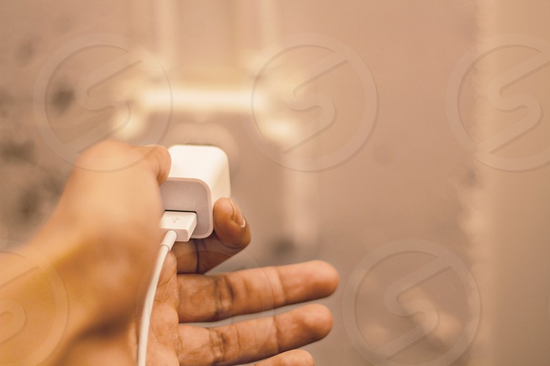 person holding white travel adapter inside socket plate photo