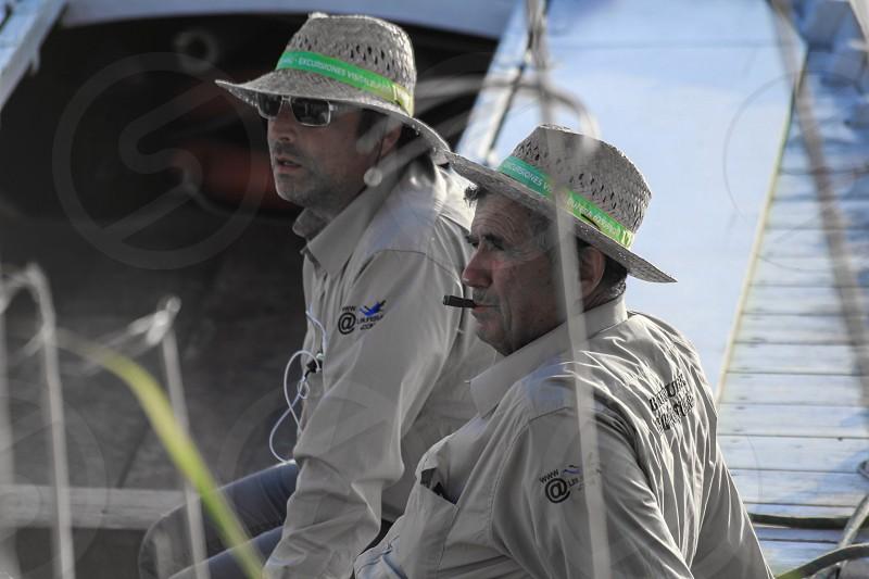 2 men in beige fisherman's coat sitting on boat during daytime photo