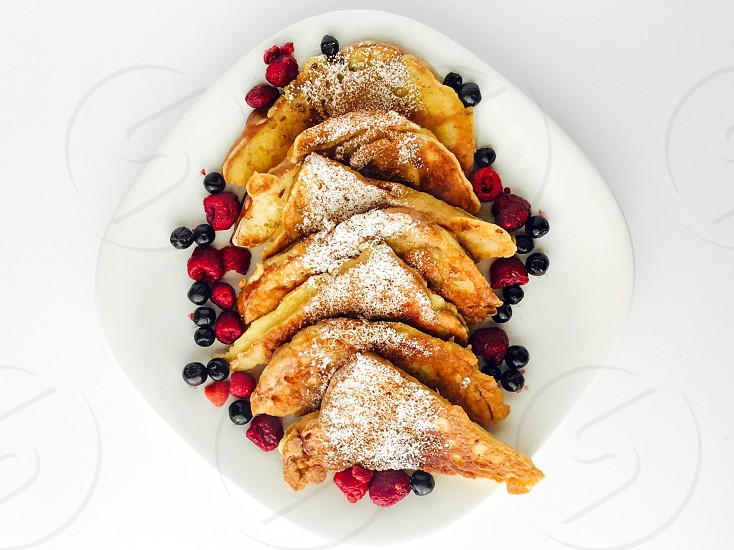 On the Table - Overhead view of French toast sprinkled with powdered sugar and cinnamon surrounded by fresh blueberries and raspberries on a white plate white background photo