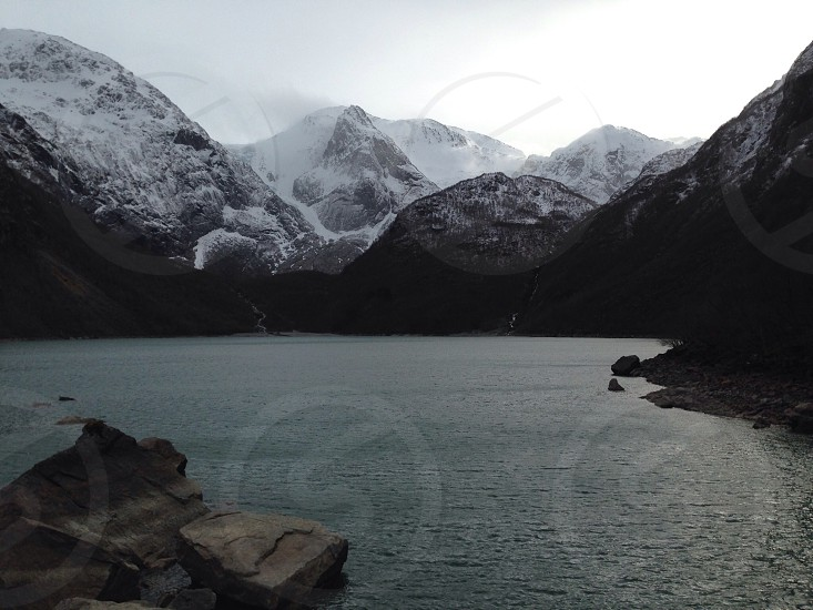 A lake and snow covered mountains in Norway in the winter. photo