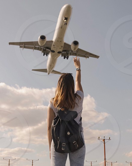flight sky looking up point of view watch pointing angle low angle girl people from behind travel traveler photo