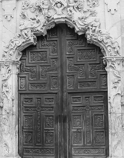 Vintage door surrounded by cheribs and laden with crosses. photo
