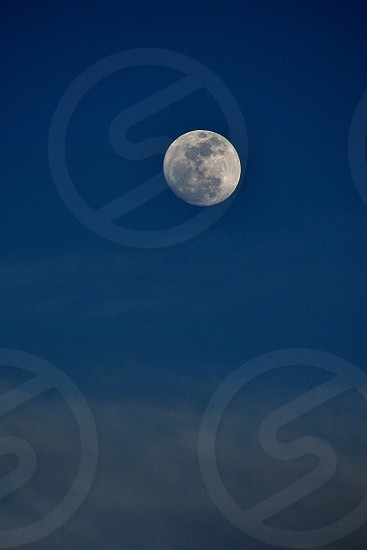 Full moon rising during the day blue sky moon photo