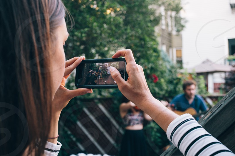woman holding a smartphone taking a picture photo