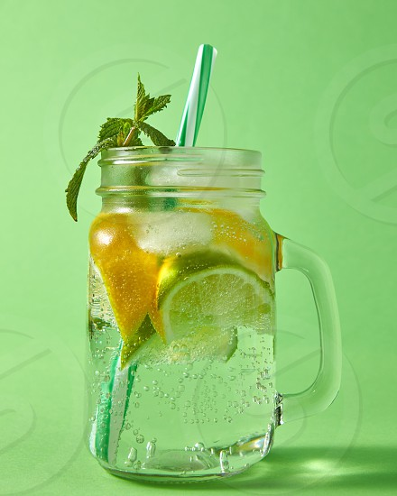 Summer natural sparkling fresh lemonade in mason glass jar with large bubbles of air on a green background. Concept of cold alcoholic or non-alcoholic summer drinks. photo
