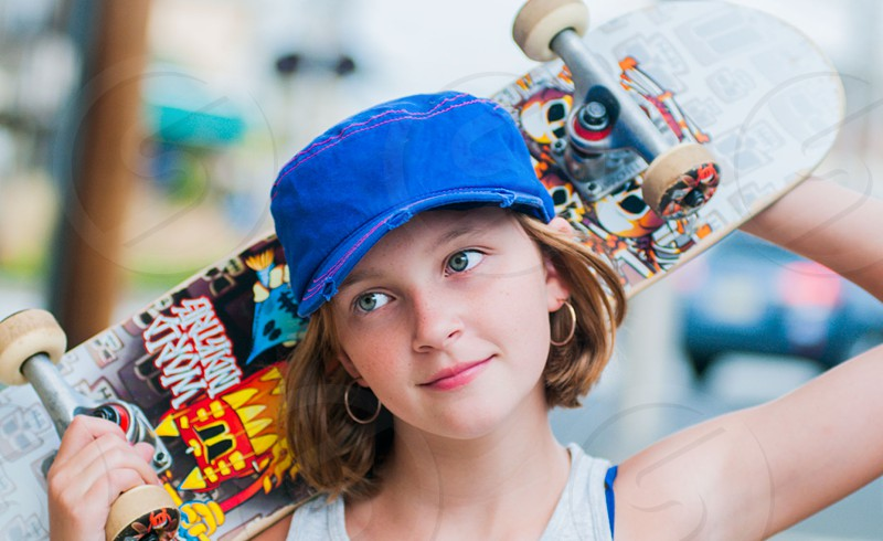 girl with blue baseball cap and hoop earrings holding skateboard behind head photo