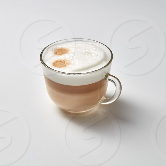 A cup of fragrant cappuccino with a smile face on a gray background with a copy of the space. Top view photo