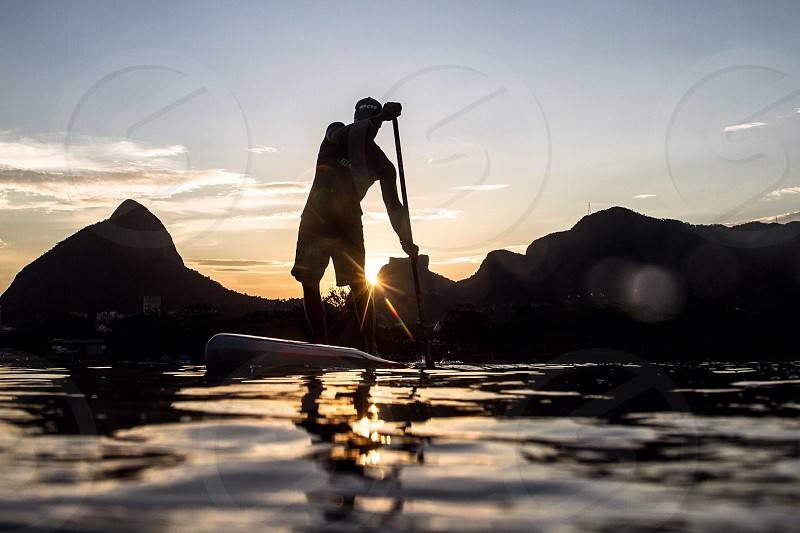silhouette of man while padding boat pedal in body of water photo