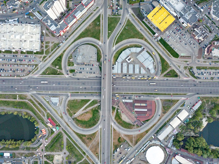 Kyiv district Poznyaki road junction with cars around the building shopping centers with parking lots part of the park and river Ukraine. Drone photograph photo