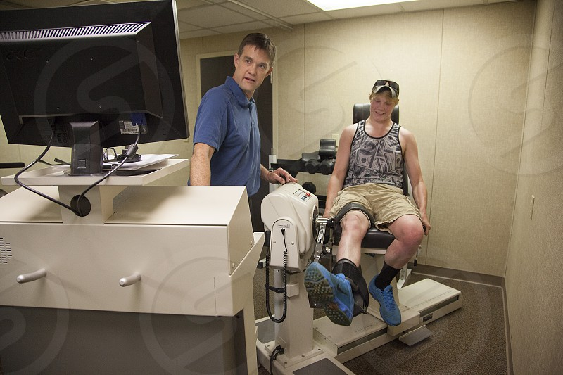 Physical therapist works with a patient during his exam and checkup required for employment photo