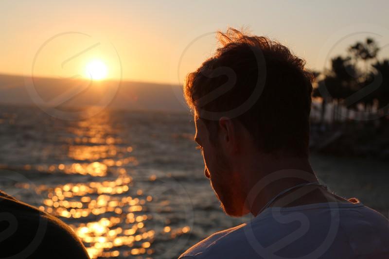 man wearing white white crew-neck shirt while watching on sunrise photo