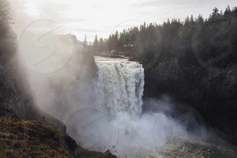 foggy waterfall crashing over a cliff with pine trees in the distance photo