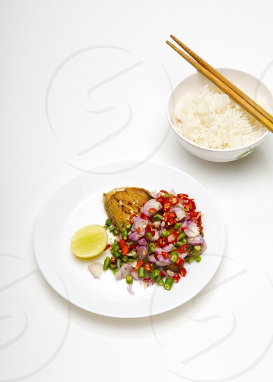 Spicy Deep Fried Salted Fish With Rice on white background (Thai Food) - Pla Kem Tod photo