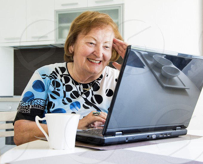 Senior woman learning how to use laptop photo