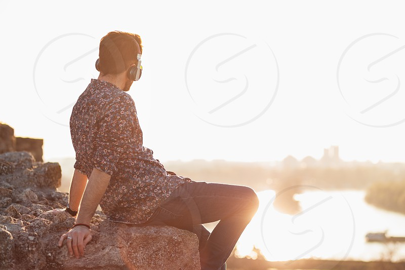 Young man enjoying listening to the music on headphones in sunset photo