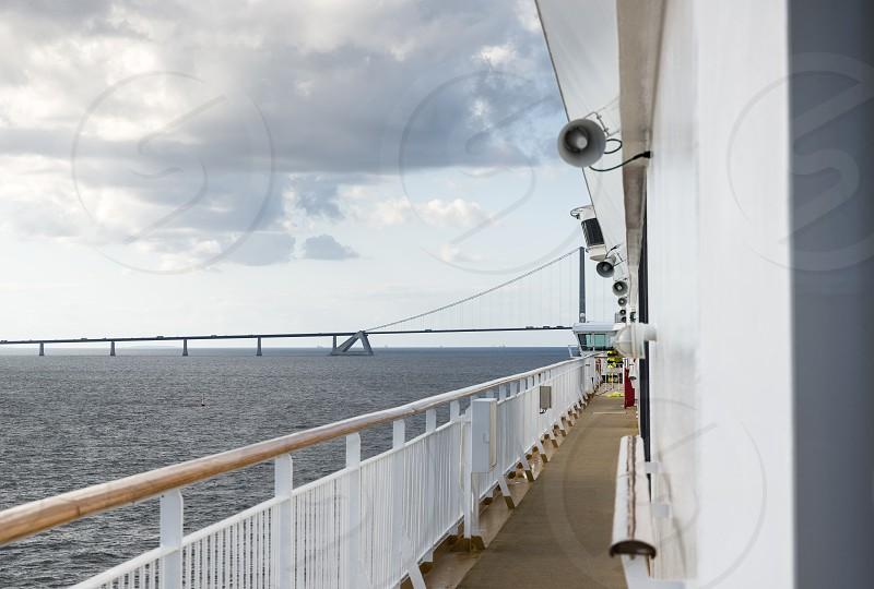 cruise ship crossing the great belt bridge at denmark at the danish islands photo