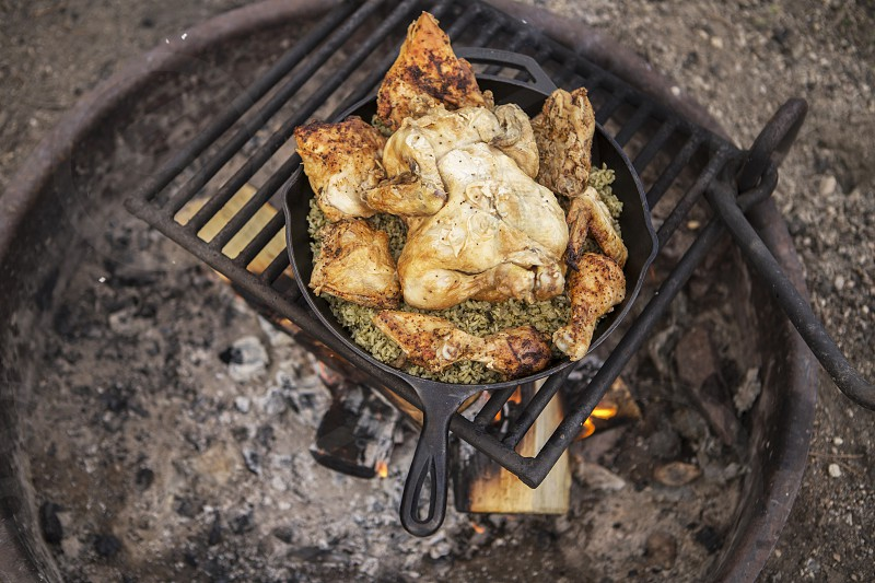 cooking chicken over open flame while camping photo