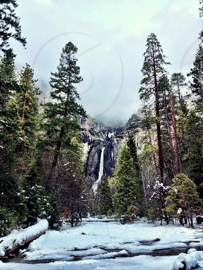 waterfall in foggy mountains with snow covered river photo