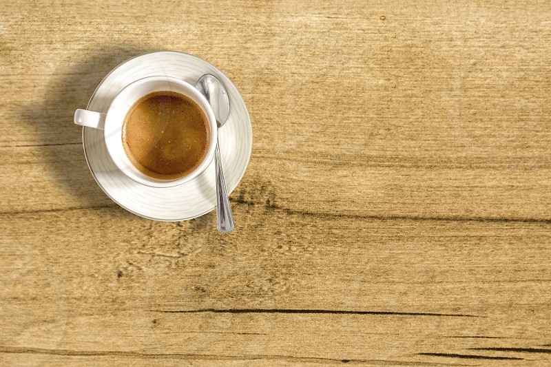 top view of a small cup of coffee on a wooden table. Taking a break with a coffee photo