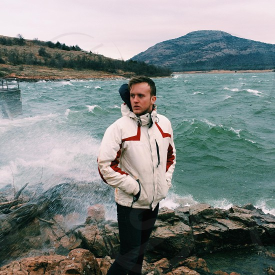 man in white coat by the shore photo