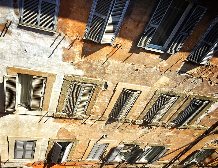 Facade of an ancient residential building with patterned windows and shutters photo