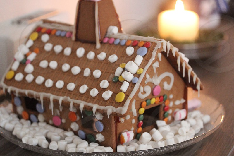 brown ginger bread house surrounded by white small marshmallows photo