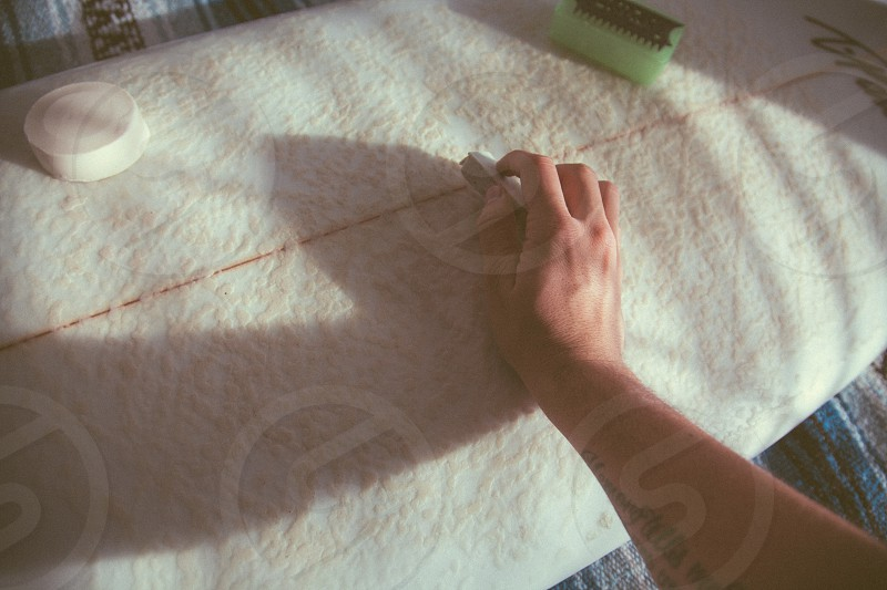 person holding marker leaning on white textile photo