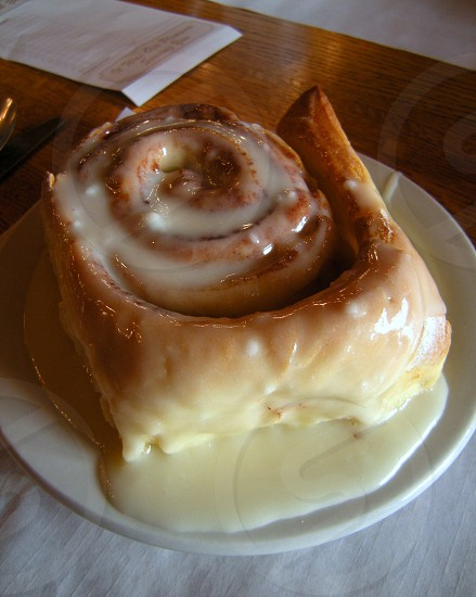 Saucer sized iced cinnamon roll on saucer with guest check in background photo