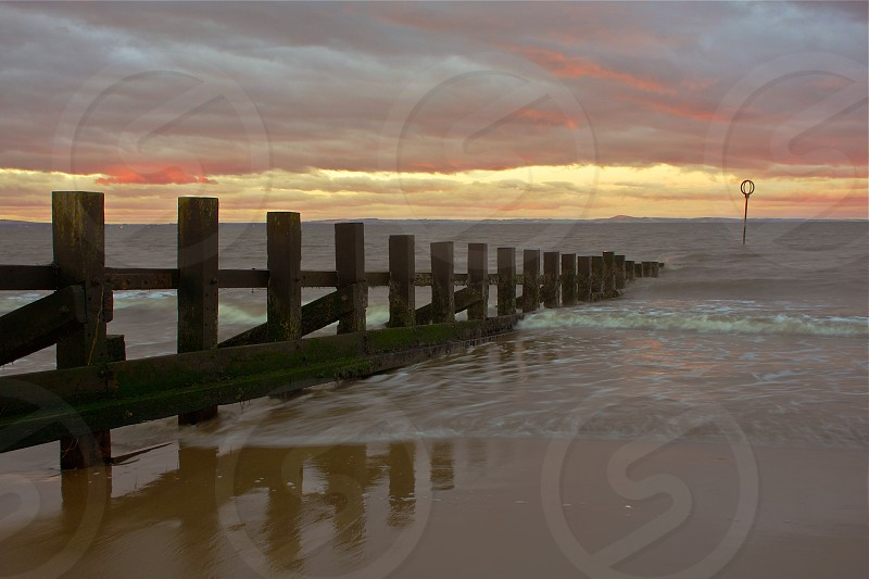 Seascape of surf and groin (barrier sea wall) from Portobello Beach Scotland at sunset. photo