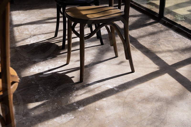 close up wooden chair legs with shadow and light on grunge cement ground photo
