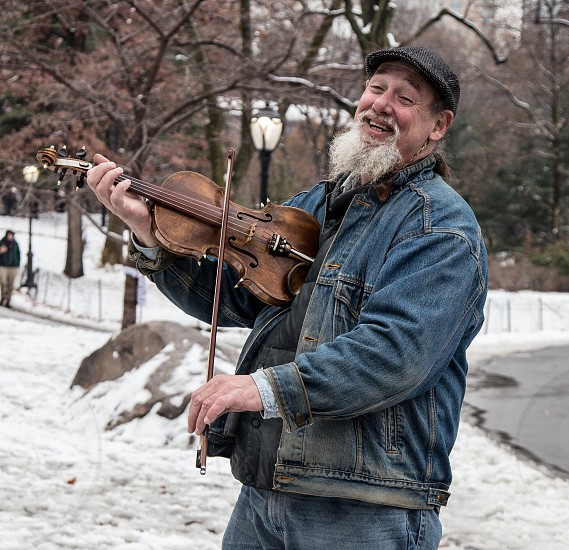 Happy man playing the fiddle violin in Central Park New York.  Snow covers the ground.  Winter. photo