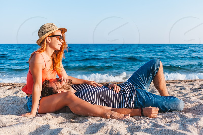 Young couple in love lying on the beach enjoying photo