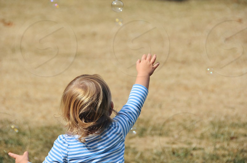 Child reaching for bubble photo