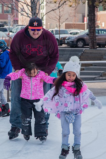 Children being helped ice skating by adult in outdoor skating area Lakewood Colorado photo