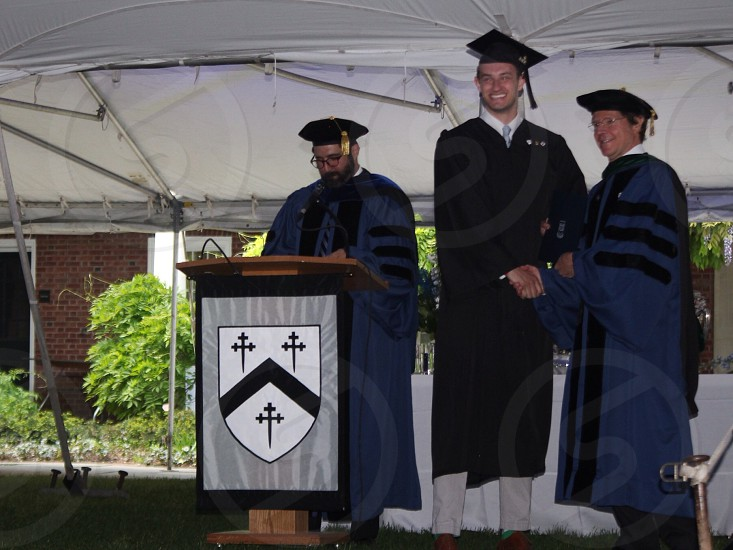 3 men with blue and black graduation robe on stage photo