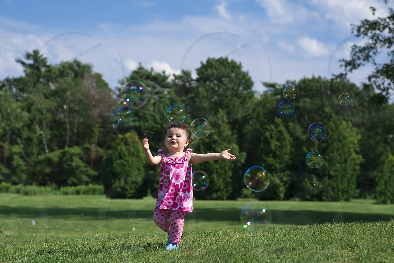 Little girl catching bubbles in the park photo