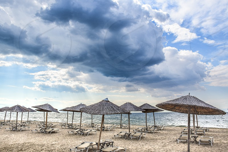 gray parasols by the seashore under gray and clouds and blue sky during daytime photo