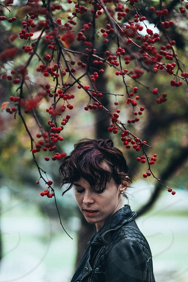 woman in black leather jacket standing under tree with red cherries in branches photo