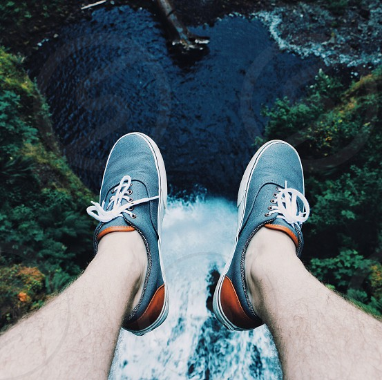 person in blue and brown lace up sneakers sitting on edge of cliff over cascading waterfalls during daytime photo