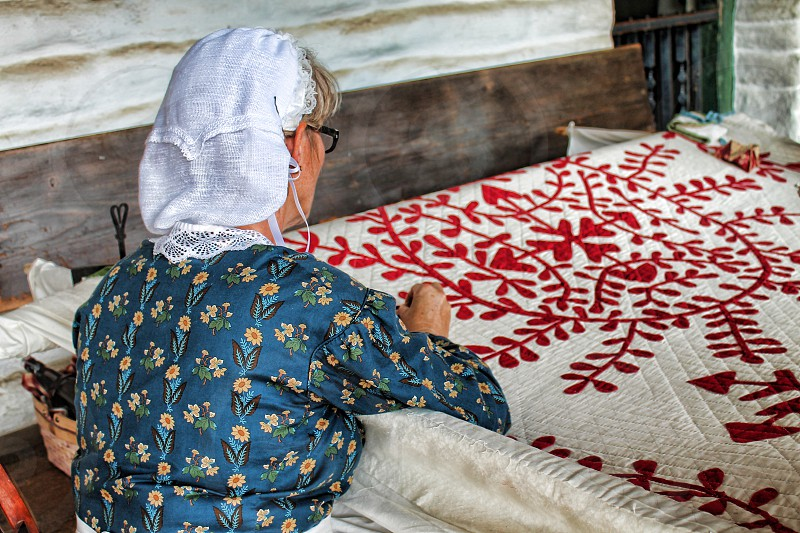 Seen from behind a woman dressed in vintage clothing quilts. photo