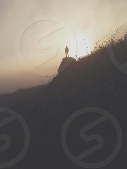 man on rock silhouette photo