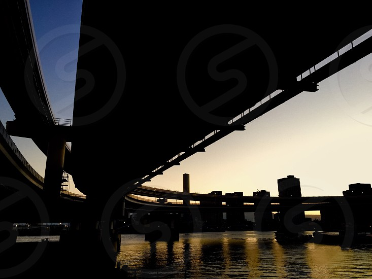 silhouette of bridge by water under white cloudy blue sky photo